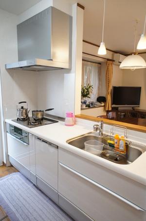 間仕切壁を一部取り除きリビングとダイニングとのつながりを作ったことで、開放的な空間に。吊戸棚をなくす代わりに背面の壁一面に収納を採用。扉を白で統一することで、一日中明るい空間になった。家電品・食器などの収納力が大幅に増えた為、すっきりとしたキッチンに。