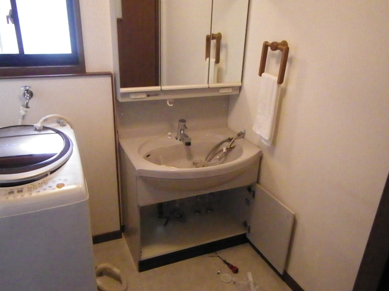20年前の洗面台ですが、陶器のボウルや収納の扉材は日頃の使い方もあって痛みが少なかったので、取替え部品の対応を調べ、給水栓と排水部品の取替えを行いました。水栓が白いプラスチックからメッキに変わっただけで印象がずいぶん違います。