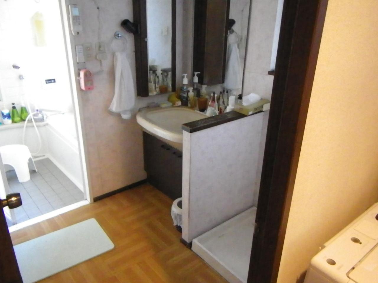 水漏れを起こしてしまった洗面台。使用年数も25年を超え、パッキンやシャワーホース部など水漏れを起こしてしまう可能性が高まります。写真は仕上げ床材までご主人様が手直しされきれいに見えますが、所々段差が気になります。